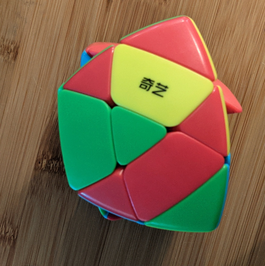 Photo of a scrambled pyramorphix twisty puzzle showing three red triangle sides of center pieces
